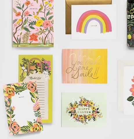 This is a laid out display of several cards, one floral, one rainbow, one floral that says Happy Easter, and one that say You make Me Smile along side a market list.