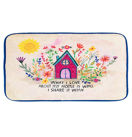 "This cream colored drying mat with blue edges has a design of a magenta house with a blue roof surrounded by purple, pink, and green flowers. Below the floral house design are the words, ""What I Love Most About My Home Is Who I Share It With"" in black lettering."