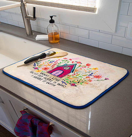 "The ""What I Love"" drying mat is shown lying on top of a marble kitchen counter. An ice cream scoop and wooden spoon are shown both sitting on top of the mat"