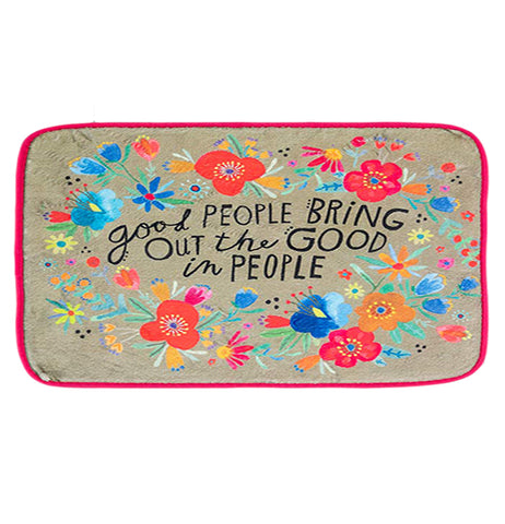 "This toap colored drying mat with red edges has a floral design of red, orange, and blue flowers covering it. In the center of the design are the words, ""Good People Bring Out The Good in People"" in black lettering."
