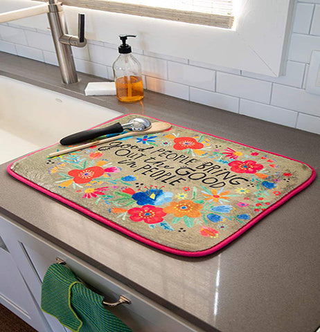 "The ""Good People"" drying mat is shown lying on top of a marble kitchen counter. An ice cream scoop and wooden spoon are shown both sitting on top of the mat."