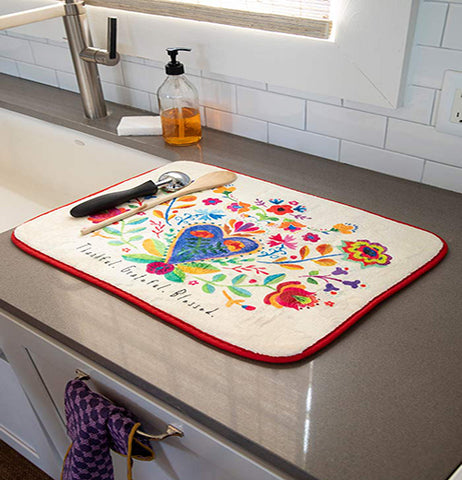 "The ""Thankful Grateful"" drying mat is shown lying on top of a marble kitchen counter. An ice cream scoop and wooden spoon are shown both sitting on top of the mat."
