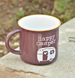"The ""Happy Camper"" Camp Mug sits on a cement table outside."
