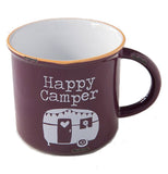 "The Camp Mug has white message ""Happy Camper"" over the RV against the eggplant colored purple background."