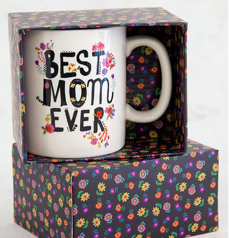The white mug is shown inside its black box, which is covered by purple, red, and yellow flowers.