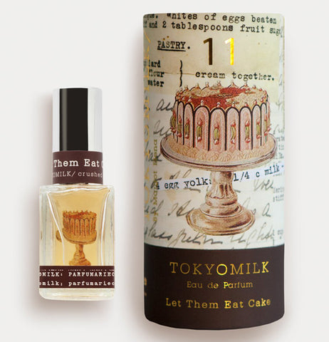 "The perfume bottle is alongside its box with the saying ""Let them eat Cake"" and a picture of a cake."