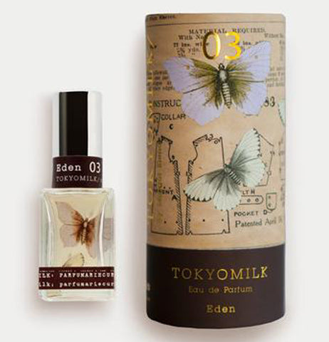 The bottle of perfume has the illustration of a moth on it and sits next to cylindrical packaging with illustrated moths over a diagram with a TokyoMilk Label on it.