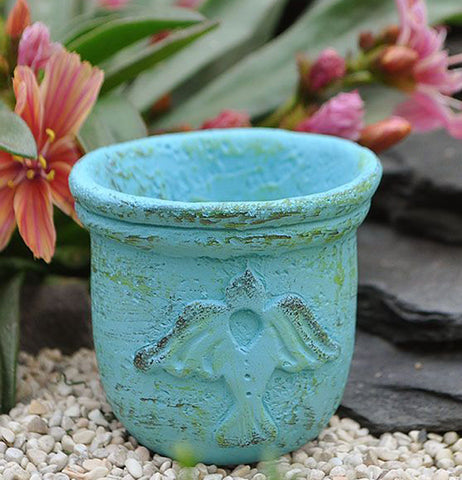 The (Mini) Blue Bird Planter has the symbol of a bird and sits outside the garden on a gravel.