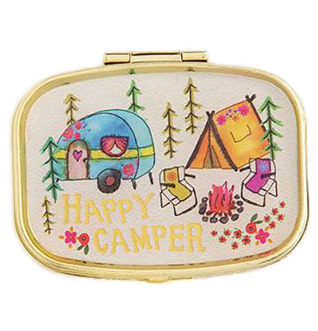 "The ""Happy Camper"" Pill Box has an illustration of a blue camper, orange tent, folding chairs, pine trees, a campfire, and the words ""Happy Camper"" on the outside with a golden rim."