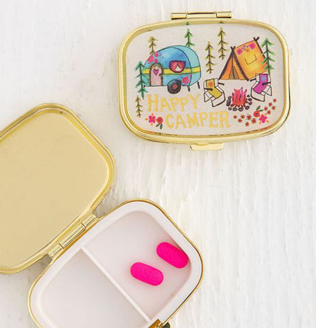 "The ""Happy Camper"" Pill Box sits with another opened pill box with two pink pills inside."