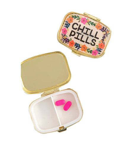 "Cream colored pill box with black words that read ""Chill Pills"" and colorful floral design sitting next to an open pillbox with gold colored lid with a white two sided compartment that has two pink pills inside one compartment."