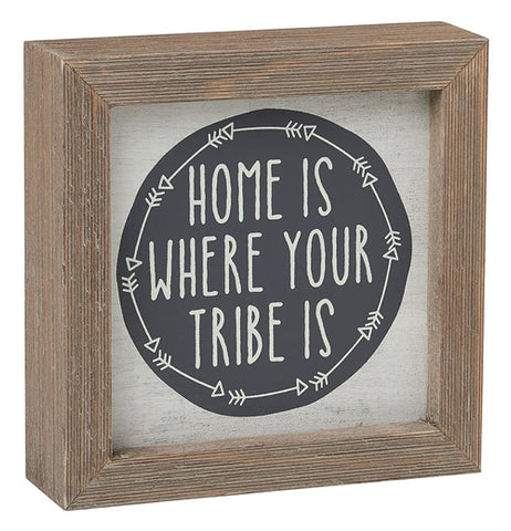 "This cream colored box sign with a brown wooden frame has a black circle with white arrows surrounding its edges. In white lettering are the words, ""Home is Where Your Tribe is""."