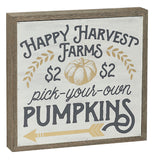 "a square box sign that has ""Happy Harvest Farms"", Pick-Your-Own"" and ""Pumpkins"" in different font styles with pictures of leaves, a pumpkin, and an arrow on it."