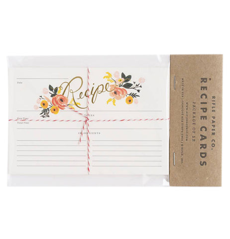 "This set of white recipe cards feature a pink and yellow peony design at the middle top. They are shown in their packaging with the words, ""Rifle Paper Co. Recipe Cards"" in black lettering."