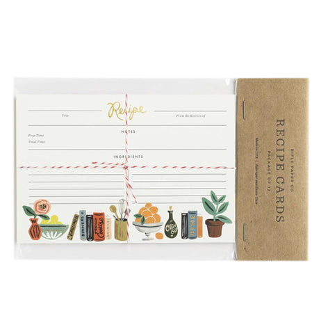 "This set of white recipe cards feature a design of potted plant, books, and fruit bowls at the bottom of the paper. They are shown in their packaging with the words, ""Rifle Paper Co. Recipe Cards"" in black lettering."