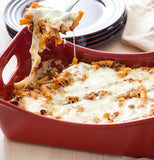 Lasagna is shown being served from the pan.