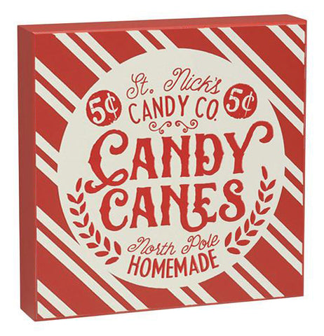 "This red and white striped wooden box sign has a white circle with the words, ""St. Nick's Candy Co. Candy Canes North Pole Homemade."" in red lettering."