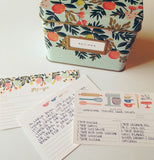 This shows some recipe cards laid out in front of a light green recipe tin box decorated with fruit.