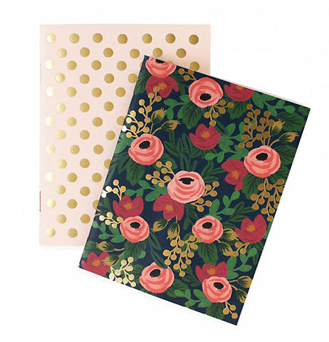 A notebook cover tilted to the right on top of the back cover. The front cover is dark blue with peach and red flowers nestled between green, white and gold smaller flowers. The back cover is a light peach color with gold polka dots covering the page spaced evenly apart . The entire photo has a white background.
