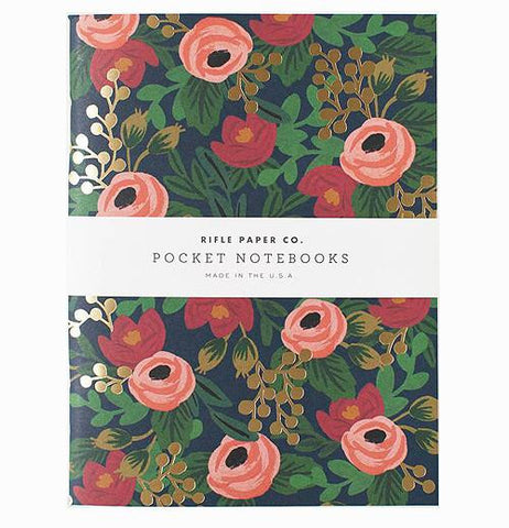 A notebook cover that is dark blue with peach and red flowers nestled between green, white and gold smaller flowers. Through the center horizontally are the words Rifle Paper Co. Pocket Notebooks Made in USA in black over a white background. The entire photo has a white background.