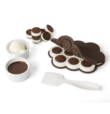 The baking dish is shown with ice cream sandwiches inside and outside it. Some dishes with cookie dough and ice cream are shown lying next to the dish and its white plastic spatula.
