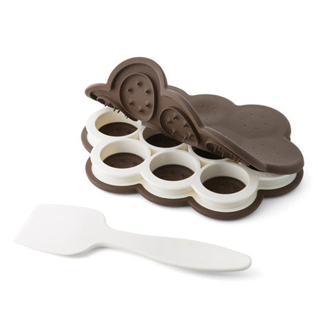 This plastic mold has 10 cylindrical shapes to put ice cream scoops in so as to make small ice cream sandwiches. It also comes with a silicone lid to provide cover when baking miniature cookies. A white plastic spatula is shown lying next to the baking dish.