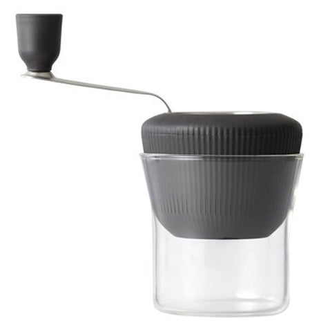 This tool has a rotating black handle and a grinding mechanism inside its black lid that fits over a big transparent glass cup.
