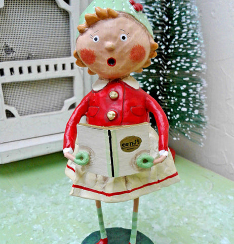 The Holly figurine with the carol book is shown standing in front of a snowy pine tree and the front door of a small house.