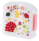 This clear plastic sandwich box shows a design of red, green, pink, and yellow hedgehogs eating red and pink mushrooms and flowers.
