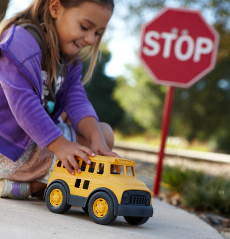 A little girl playing with a plastic school bus with a stop sign in the back ground.