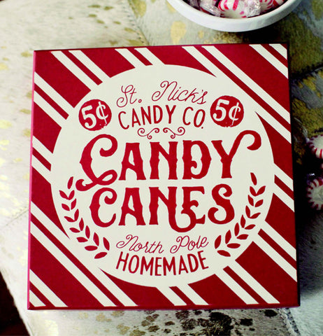 "The red and white ""Candy Canes"" wooden box sign is shown lying on a table next to a bowl of mints."