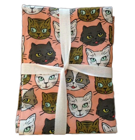 Salmon pink background with brown, black, white, and gray cat faces.