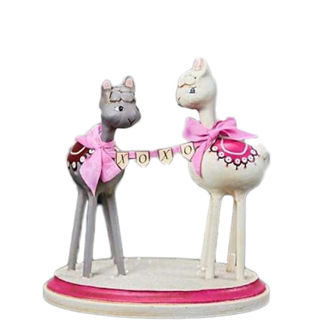 Two llama resin figurines are standing on a white and pink base. They both have pink ribbons on their neck. The left llama is gray with a black saddle. The right llama is white with a pink saddle. A pink ribbon with the letters X O X O is between them.