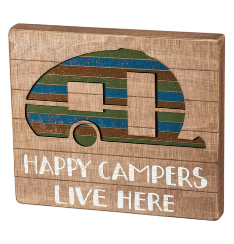 "This sign ""Happy Campers Live Here"" painted white on tanned wood below the green, red, and blue striped camper."
