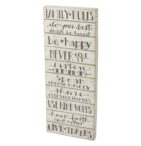 An off-white wooden sign featuring family rules written in gray lettering. Such as: always be honest, be happy, never give up, and give thanks