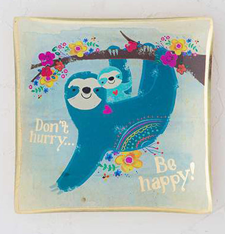 Square glass tray with image of a blue sloth and cub hanging from a flower lined tree branch with the words Don't Hurry Be Happy in gold foil laying on a table.