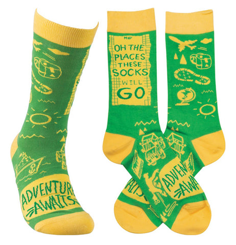 "These yellow and green socks sport the words, ""Oh the Places We Will Go, Adventure Awaits"" in green over a yellow background."