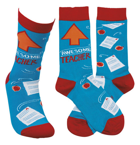 "These are blue socks with red heels, toes, and tops. They have orange arrows pointing up with the words, ""Awesome Teacher"" in red and white lettering with images of apples and graded papers on them over a white background."
