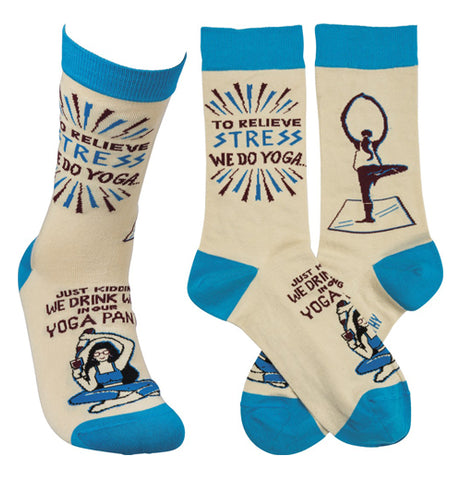 "Blue, white, and black socks with humorous black writing that says ""To Relieve Stress we do Yoga, Just Kidding We Drink Wine in our Yoga Pants"" with print images of people doing yoga."