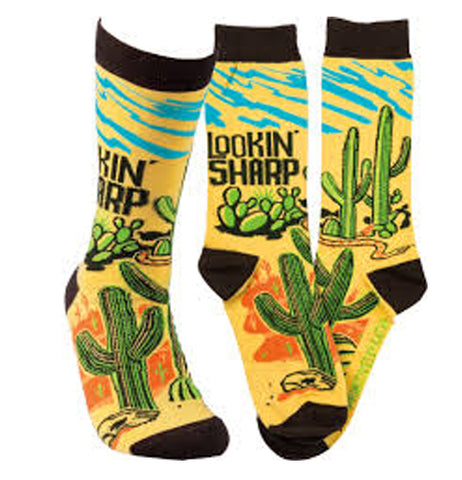 "These yellow socks have black toes, heels, and tops. A green cactus print image shows an orange desert background and wavy blue streaks at the top. Above the green cactus are the words, ""Lookin' Sharp"" in black lettering."