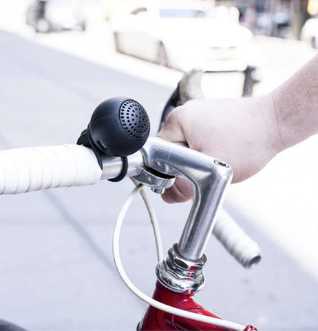 A small black speaker attached to bicycle handles.
