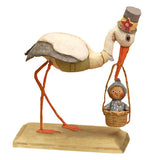 Pelican wearing a hat carrying a baby in a basket.