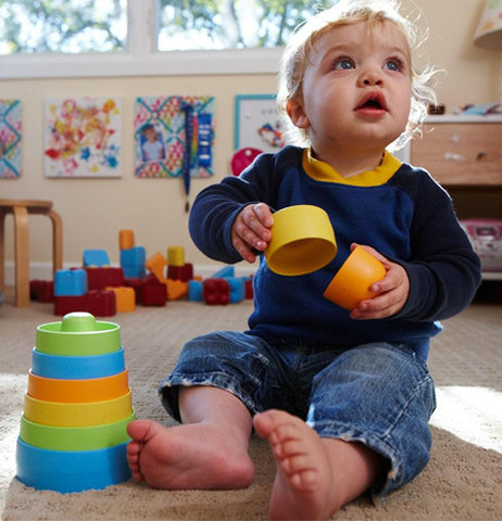 A baby is shown playing with the multi-colored stacking cups.