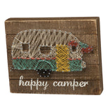 Stitchings that form a camper on a wooden brown background.