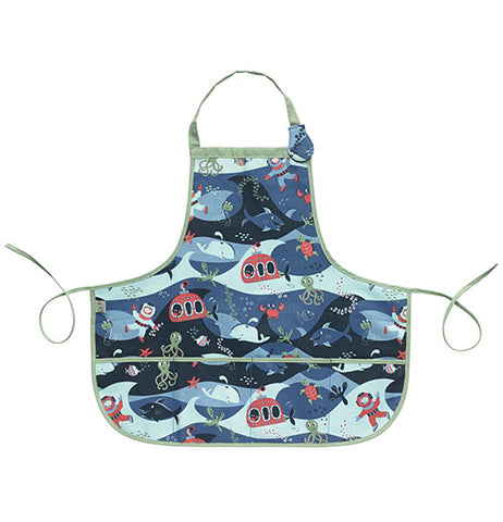 This blue kiddie apron has a design of sharks, whales, divers, and submarines covering it and green tying strings.