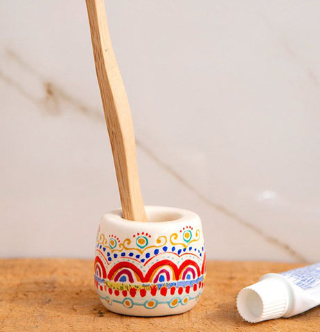 The rainbow design toothbrush holder is shown lying on a table with some toothpaste lying next to it.