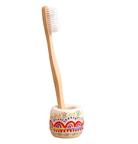 This toothbrush holder has a design of red, teal, and blue rainbow shapes covering it. A wooden toothbrush is shown sitting in it.