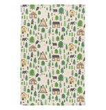 A woodland themed towel that includes pine trees, bears, and cabins.