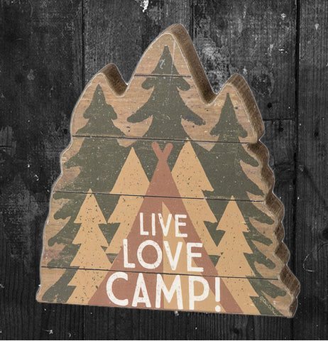 "The wooden cutout of three green pine trees back to back with a teepee in front of them and the words, ""Live, Love, Camp"" in front of the teepee now sits on a dark grey wooden background."