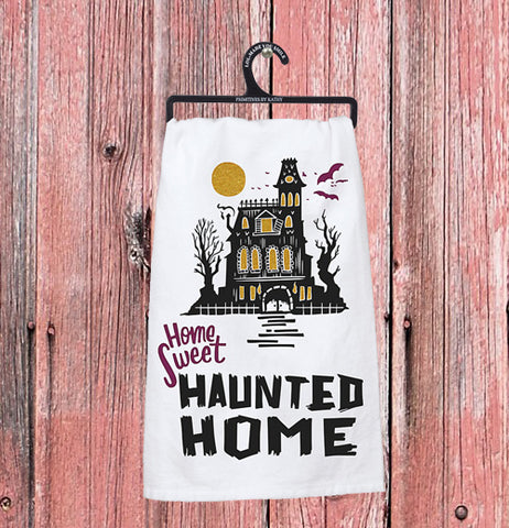 "The ""Home Sweet Haunted Home"" dish towel hangs on a pink wooden wall."
